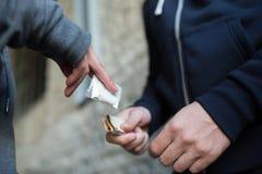 Sluit omhoog van verslaafde het kopen dosis van drugdealer stock afbeeldingen