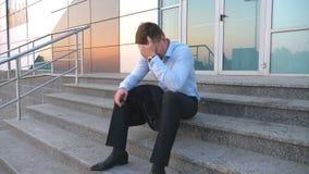 Sluit omhoog van verstoorde droevige managerzitting op treden dichtbij de bureaubouw en het schreeuwen De wanhopige jonge zakenma stock videobeelden