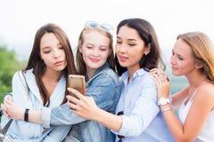 Sluit omhoog van vier mooie jonge vrouwelijke studenten die selfies doen royalty-vrije stock afbeeldingen
