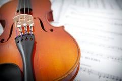 Sluit omhoog van viool op de linkerzijde met vage muziek Royalty-vrije Stock Foto