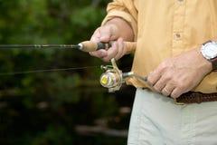 Sluit omhoog van visser windende visserijspoel stock fotografie