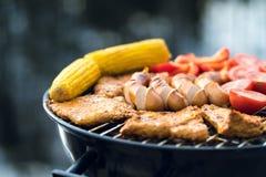 Sluit omhoog van voedsel roosterend op een grill van de houtskoolketel Royalty-vrije Stock Afbeeldingen