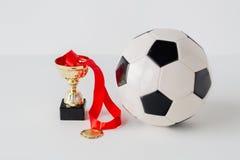 Sluit omhoog van voetbalbal, gouden kop en medaille Stock Fotografie