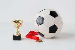 Sluit omhoog van voetbalbal, gouden kop en medaille Royalty-vrije Stock Foto