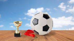 Sluit omhoog van voetbalbal, gouden kop en medaille Royalty-vrije Stock Foto's