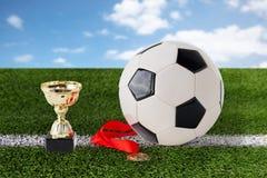 Sluit omhoog van voetbalbal, gouden kop en medaille Stock Foto