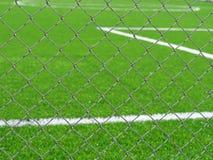 Sluit omhoog van voetbalgebied achter de omheining van de kettingsverbinding royalty-vrije stock fotografie