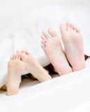 Sluit omhoog van voeten van het paar liggend in bed Royalty-vrije Stock Foto's