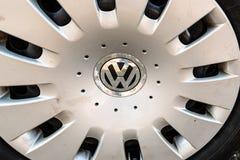 Sluit omhoog van Volkswagen-embleem op een gedeukt wiel Stock Foto's