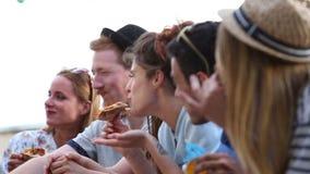 Sluit omhoog van vrienden bij een partij die in pizza genieten van stock footage