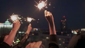 Sluit omhoog van vriendenhanden met de lichten van Bengalen of het fonkelen Zij golvende handen die op het stadsdak bij nacht bli stock videobeelden