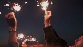 Sluit omhoog van vriendenhanden met de lichten van Bengalen of het fonkelen Zij heffen handen aan hemel op, die op het stadsdak b stock video