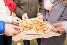 Sluit omhoog van vriendenhanden in openlucht etend pizza Stock Foto's