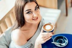 Sluit omhoog van vrouw die camera bekijken, kop van koffie houden stock foto's