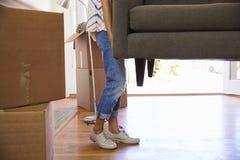 Sluit omhoog van Vrouw die de Bewegende Dag van Sofa Into New Home On dragen royalty-vrije stock afbeeldingen