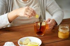 Sluit omhoog van vrouw die gember toevoegen aan thee met citroen Stock Afbeelding