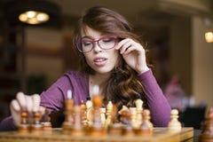 Sluit omhoog van vrouw die in glazen schaakspel spelen Kijkt aan boord royalty-vrije stock afbeelding
