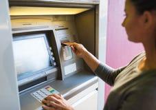 Sluit omhoog van vrouw die kaart opnemen aan ATM-machine stock fotografie
