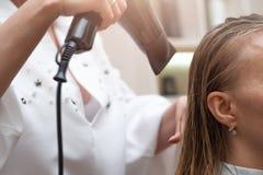 Sluit omhoog van vrouw en kapper met een hairdryer stock fotografie