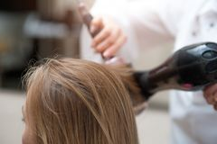 Sluit omhoog van vrouw en kapper met een hairdryer royalty-vrije stock afbeeldingen