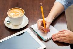 Sluit omhoog van vrouw het schrijven aan notitieboekje met potlood Stock Foto's