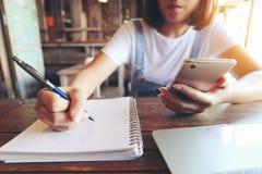 Sluit omhoog van vrouw het schrijven op het Witboek door een pen en een hand houdend mobiele smartphone op de houten lijst in kof royalty-vrije stock afbeeldingen