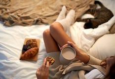 Sluit omhoog van vrouw met cacaokop en koekje in bed royalty-vrije stock afbeeldingen