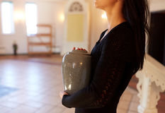 Sluit omhoog van vrouw met crematieurn in kerk stock afbeeldingen