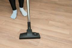 Sluit omhoog van vrouw met de schoonmakende vloer van de benen stofzuiger thuis Stock Foto's