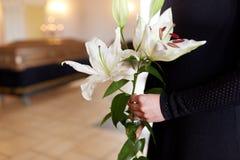 Sluit omhoog van vrouw met leliebloemen bij begrafenis royalty-vrije stock afbeelding