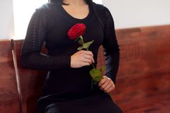 Sluit omhoog van vrouw met rozen bij begrafenis in kerk stock foto's
