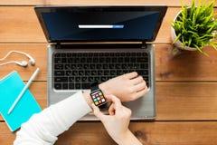 Sluit omhoog van vrouw met slimme horloge en laptop Stock Foto