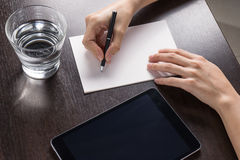 Sluit omhoog van vrouw met tablet en schrijf een document op houten lijst Royalty-vrije Stock Foto's