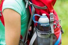Sluit omhoog van vrouw met waterfles in rugzak Royalty-vrije Stock Foto