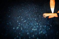 Sluit omhoog van vrouw in pak tegen de donkere achtergrond van bokehlichten Stock Foto's