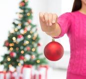 Sluit omhoog van vrouw in sweater met Kerstmisbal Royalty-vrije Stock Afbeeldingen