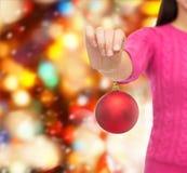 Sluit omhoog van vrouw in sweater met Kerstmisbal Stock Foto