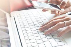 Sluit omhoog van vrouwelijke hand gebruikend mobiele telefoon en laptop computer stock foto