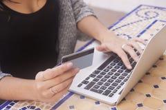 Sluit omhoog van vrouwelijke handen verrichtend online betaling Vrouwenzitting bij royalty-vrije stock afbeeldingen