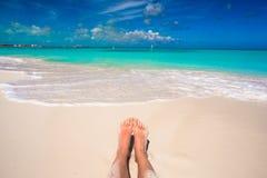 Sluit omhoog van vrouwelijke voeten op wit zandig strand Stock Afbeeldingen