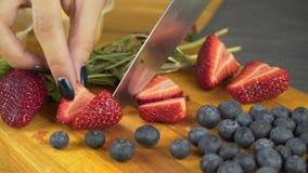 Sluit omhoog van vrouwen` s handen die en aardbeien snijden snijden stock videobeelden
