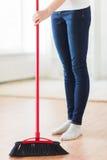 Sluit omhoog van vrouwenbenen met bezem vegende vloer Stock Fotografie