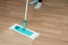 Sluit omhoog van vrouwenbenen met zwabber schoonmakende vloer thuis Stock Foto