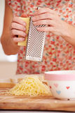 Sluit omhoog van Vrouwengrating Kaas in Keuken Stock Foto