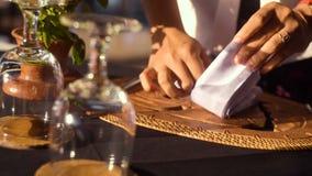 Sluit omhoog van vrouwenhand die wit servet op lijst vouwen stock video
