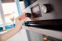 Sluit omhoog van vrouwenhand plaatsende het koken wijze op oven royalty-vrije stock foto