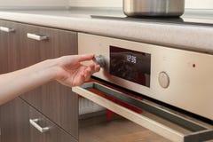 Sluit omhoog van vrouwenhand plaatsende het koken wijze op oven Stock Foto's