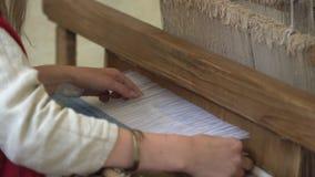 Sluit omhoog van vrouwenhanden die blauw en wit patroon op weefgetouw weven Traditionele het weven techniek stock video