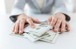 Sluit omhoog van vrouwenhanden die ons tellen dollargeld Royalty-vrije Stock Foto's