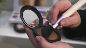 Sluit omhoog van vrouwenhanden met de holding van de make-upborstel blozen stock video